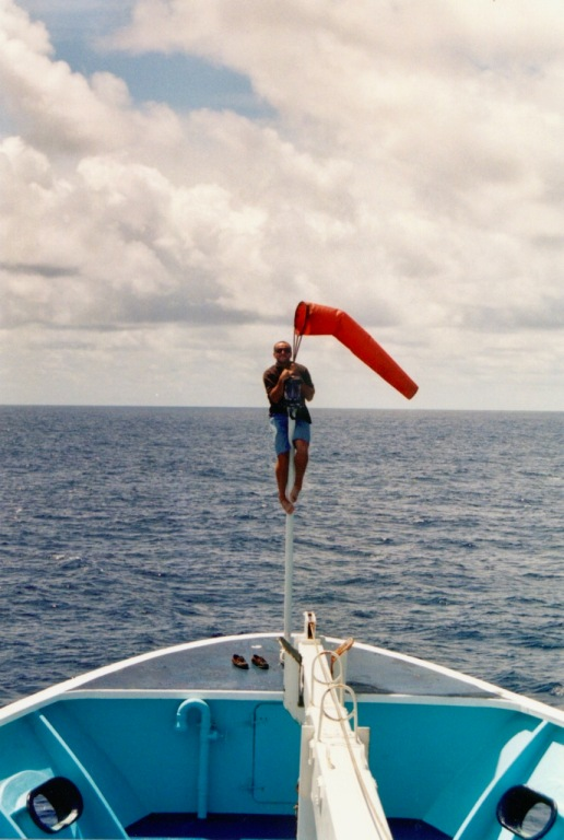 """Jean """"JC"""" (helicopter pilot) climbing up to fix the windsock at the bow of the Auro"""
