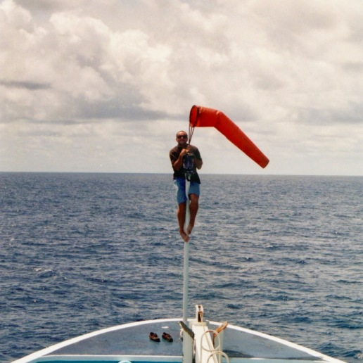 "Jean ""JC"" (helicopter pilot) climbing up to fix the windsock at the bow of the Auro"