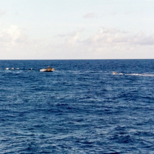 Skiff setting the net with one of the speedboats making noise at the net opening