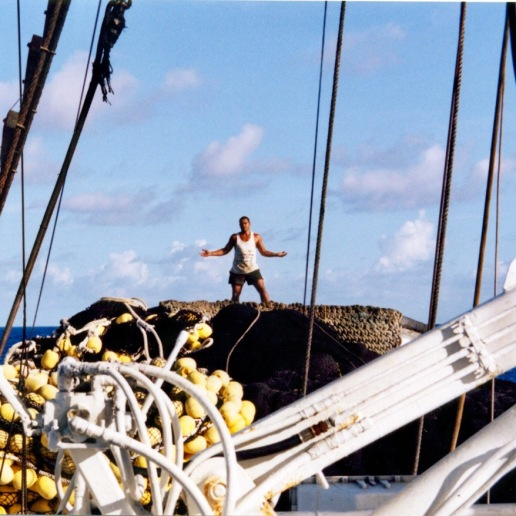 Tino (assistant skiffman) standing on the net at the rear of the Auro